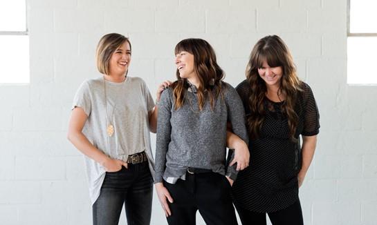 Drei Frauen stehen in einer Gruppe zusammen und unterstützen sich in einem Frauennetzwerk.